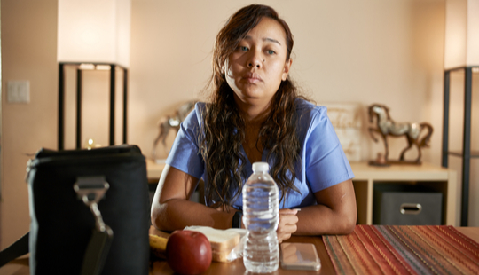 healthcare worker sitting at table looking sad