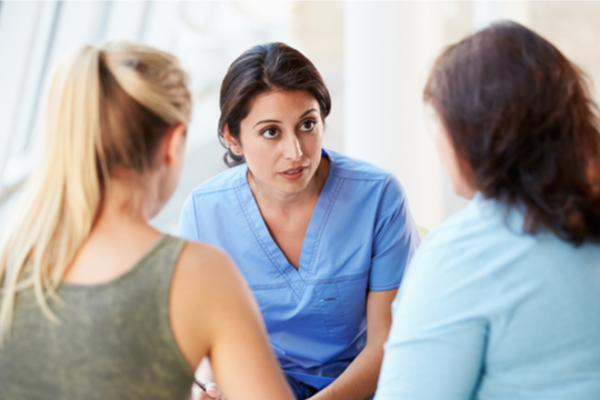 A female nurse talks earnestly with family members.