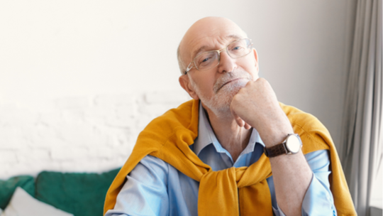 An older man with a sweater over his shoulders looks thoughtfully into the camera.
